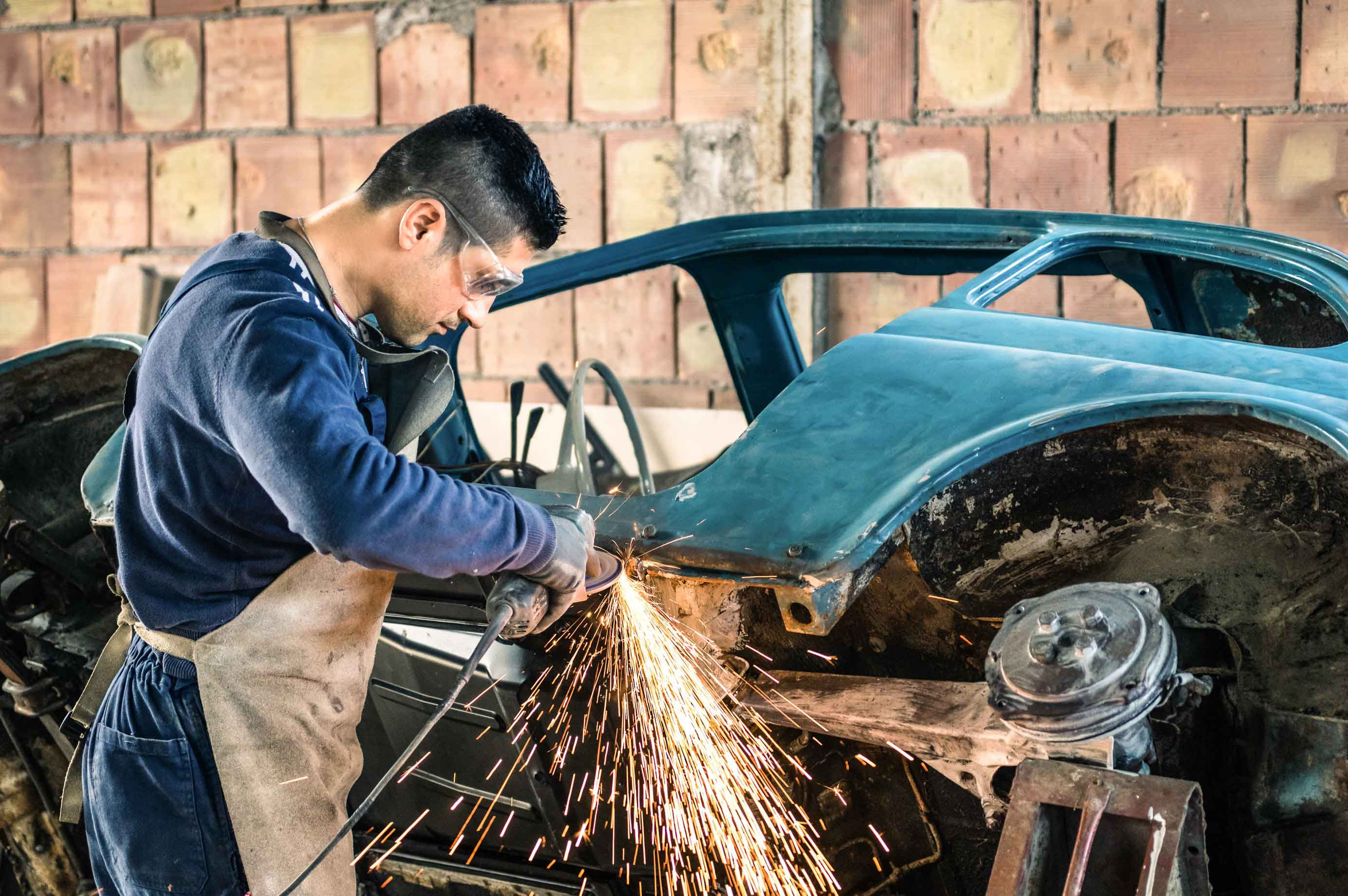 Automotive worker grinding a frame on an old car and creating sparks and dust from power tools